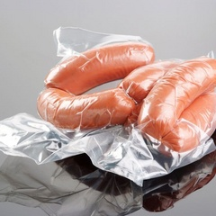 Vacuum-packed smoked sausages in plastic casings